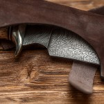 71945736 - hunting damascus steel knife handmade in sheath on a brown wooden background, closeup