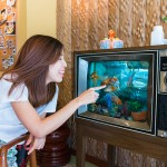 81630970 - an asian girl is playing with the goldfish in the tv fish tank, strange furniture