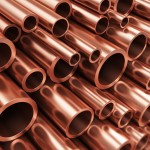 Creative abstract heavy non-ferrous metallurgical industry and industrial manufacturing business production concept: heap of shiny metal copper pipes with selective focus effect