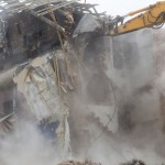 The destruction of the walls of the old building and the cleaning of construction debris with a bucket of an excavator.